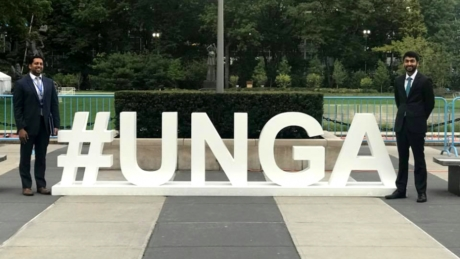 """Two men stand on both sides of a large sign reading,""""#UNGA"""""""