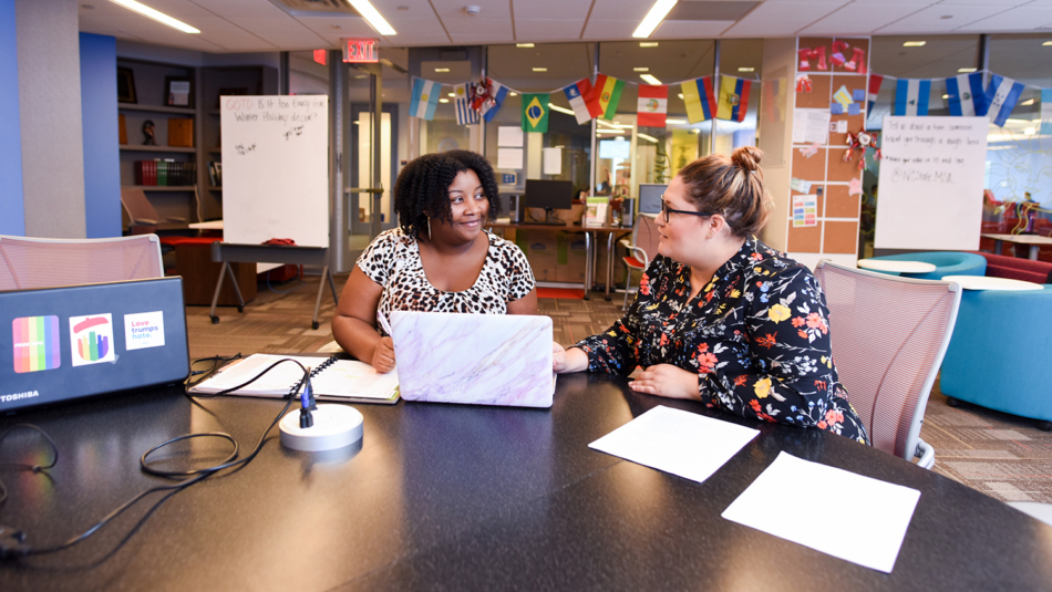 Staff Leah Young and April Hammonds work together in the lobby of Multicultural Student Affairs.